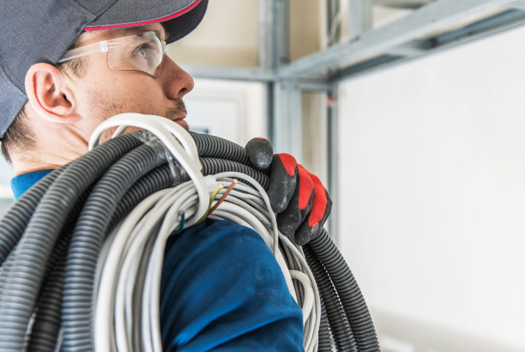 electrician carrying cables over right shoulder