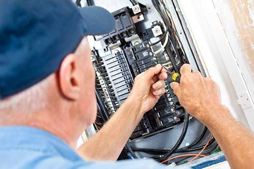 Electrician installing a new circuit breaker.
